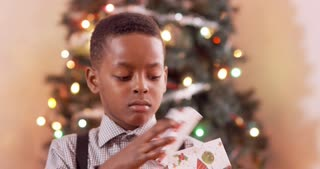Young boy super excited after he opens his Christmas present.