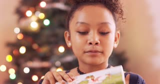 Young girl opens a present and is surprised.