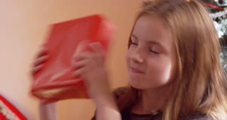Young girl shakes a Christmas present, curious to know what is in it.