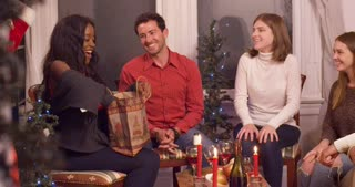 Young woman opens present with friends on Christmas eve