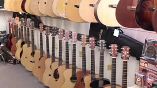 Wide shot pan music store acoustic guitars
