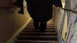 Woman carefully walking down stairs