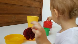 A liitle baby boy plays with dishes. Cooking a breakfest in toy kitchen