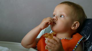 A little baby boy eats bread sitting in a child chair on kitchen
