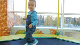 A little baby boy jumping on a trampoline