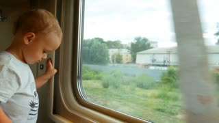 A little baby boy looking in the train window