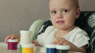 A little baby boy plays in room with cans making tower