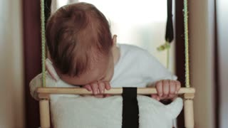 A little baby boy sleeping in swing at home