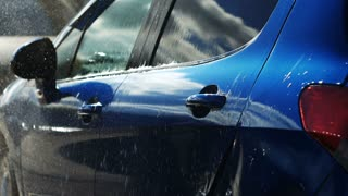 Blue car washed by hand using a water jet wash in a shiny day