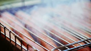 Bratwurst sausages cooking on a grill barbecue