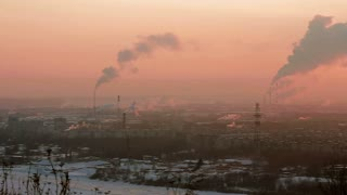 Cityscape with smoke stacks on sunset