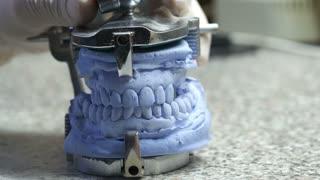 Closeup of a dental technician making of denture in a dental lab.