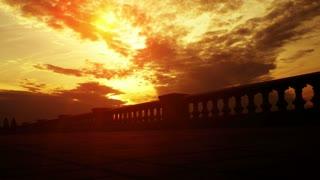 Cyclist riding on summer evening embankment. Beautiful evening sunset sky