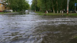Flooded road cars moving slowly in deep puddles.