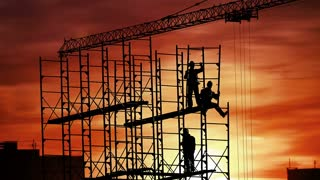 Group of workers build house on sunset sky background.