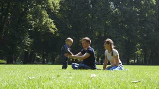 Happy family with baby sitting on the grass in summer park