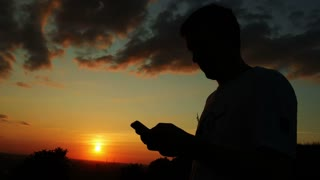 Man talking by mobile phone on sunset sky background