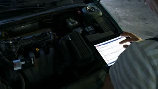 Mechanic in a auto repair shop checking engine using a digital tablet