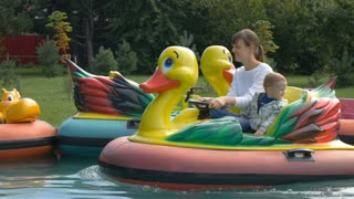 Mother and her little baby boy are rides on duck attraction in a park water pool