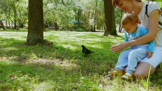 Mother and her little baby boy feeding squirrel in summer park. Squirrel eats nuts from hand.