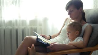 Mother and her two years old baby boy are reading book sitting in armchair in sunny room