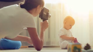Mother making movie of her baby boy using retro movie camera in sunny living room.