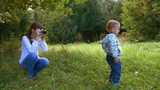 Mother taking a pictures using retro film camera of her baby boy in a summer park