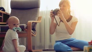 Mother taking a pictures using retro film camera of her baby boy in sunny living room.
