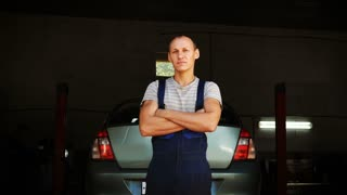 Portrait of a young mechanic standing near car lift