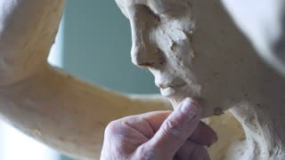 Scultor modeling woman sculpture in modeling clay