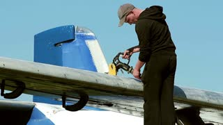 Service staff fueling commercial airplane.