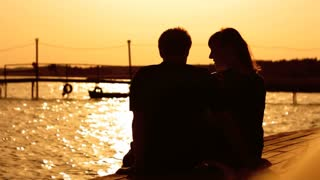 Silhouettes of two young couple enjoying the sunset on the sea coast