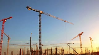 Timelapse cranes working in construction site of football stadium on sunset