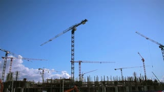 Timelapse of construction cranes working on stadium construction site