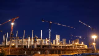Timelapse with cranes working on construction site on night sky background. Concept of working construction yard.