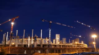 Timelapse with cranes working on construction site on night sky background. Concept of working construction yard