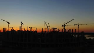 Timelapse with silhouette of cranes working on construction site on sunset sky background. Aerial shooting
