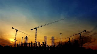 Timelapse with silhouette of cranes working on construction site on sunset sky background.