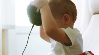 Two years old baby boy listening music in headphones