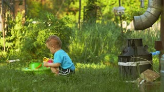 Two years old baby boy plays on backyard in garden with water can
