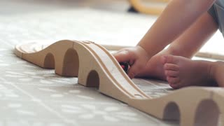 Two years old boy plays with wooden railroad in a sunny room