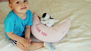 """Two years old boy sitting on bed and reading sign """"I LOVE YOU"""" and smiling."""