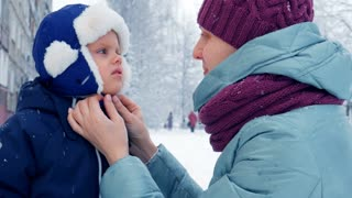 A mother and her baby boy playing outside in the snow