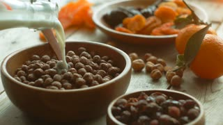 Cinemagraph chocolate cereal balls and milk pouring into wood bowl