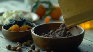 Cinemagraph chocolate cereal balls falling into wood bowl
