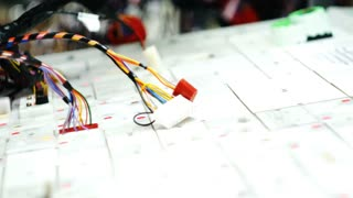 factory worker hands are working on machine and connecting electrical wires