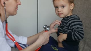 Kid doctor examing happy baby boy with stethoscope.