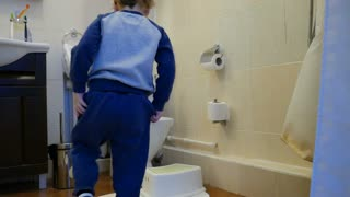 Little boy use the toilet in the bathroom of his house