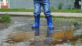 Low angled shot of baby walking and jumping in the pool in the rubber boots
