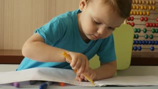 Preschool boy focused on drawing by felt-tip pen